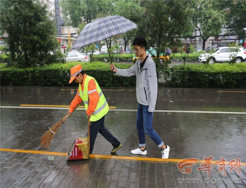 大学生为保洁撑伞40分钟