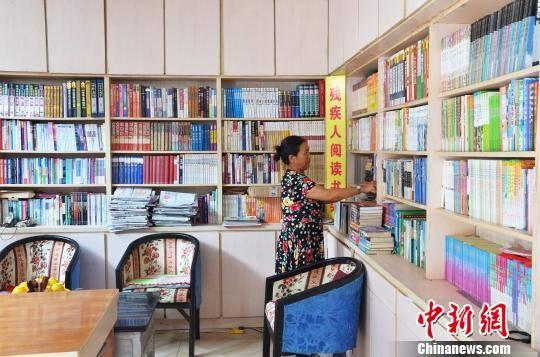 图为刘石江的妻子在整理读物。 叶清晖 摄