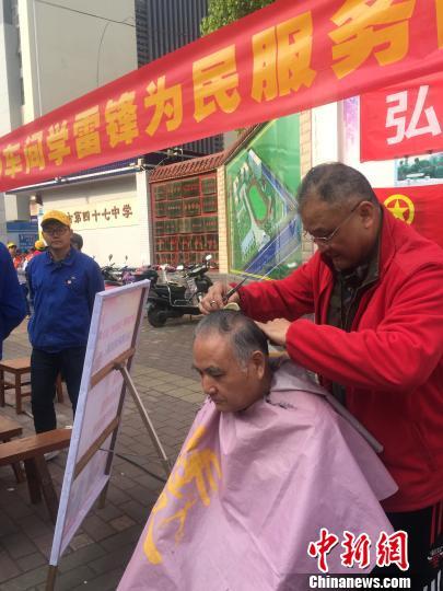 3月10日,广西柳州机车车辆厂的一名老年志愿者在为市民提供免费理发服务。 周潇男 摄