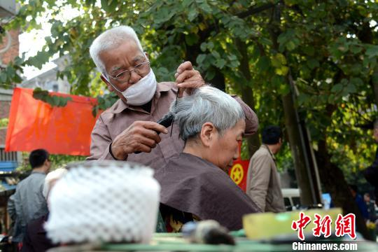 3月10日,75岁的志愿者韦天华正在市民提供免费理发服务。 孙�S飞 摄