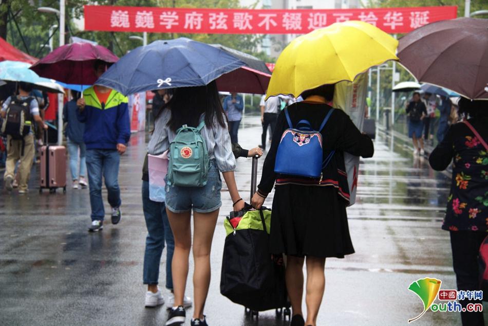 一手打伞一手拿行李的一家人有